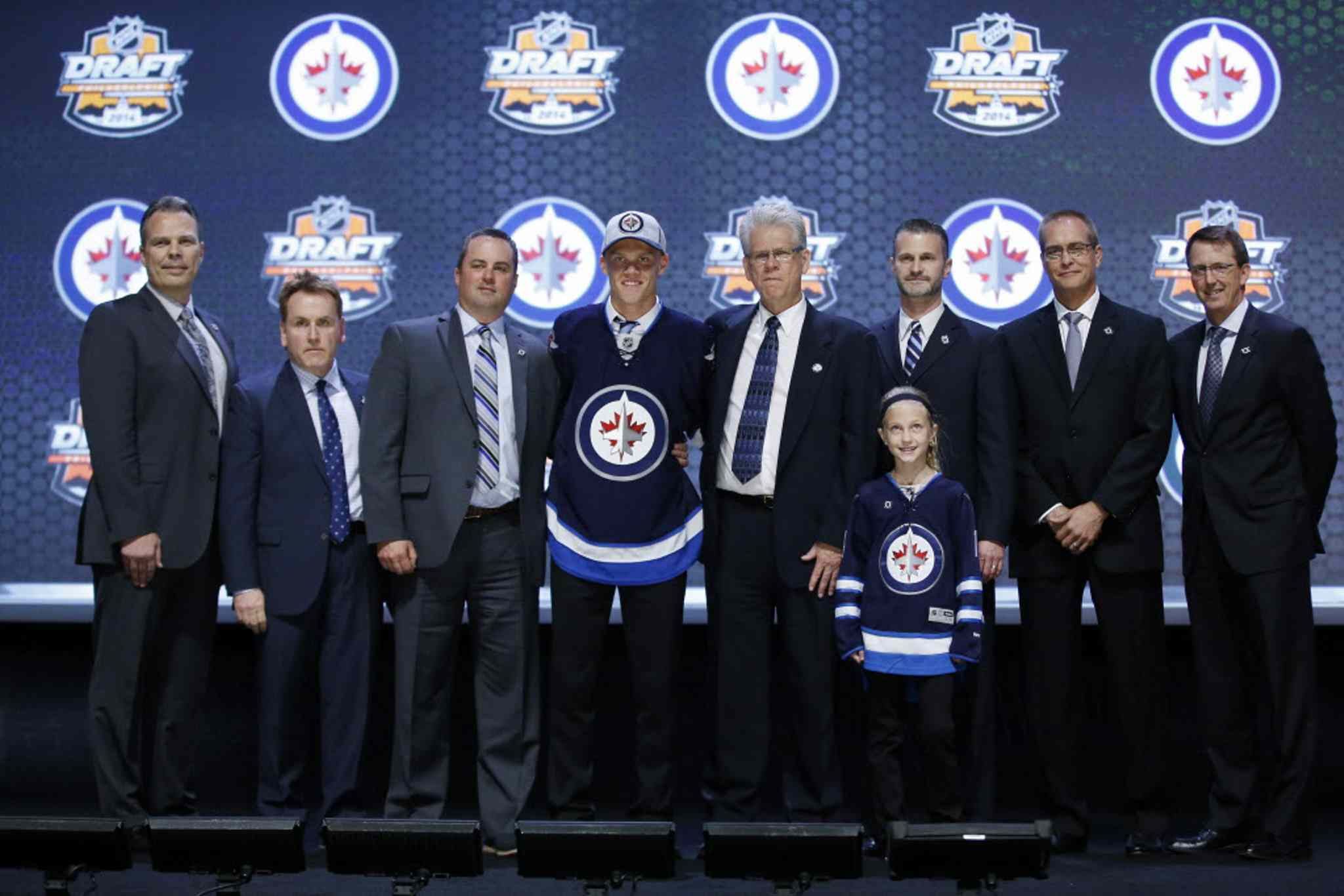 Nikolaj Ehlers stands with Winnipeg Jets officials after being chosen ninth overall during the first round of the NHL hockey draft, Friday, June 27, 2014, in Philadelphia. (AP Photo/Matt Slocum)