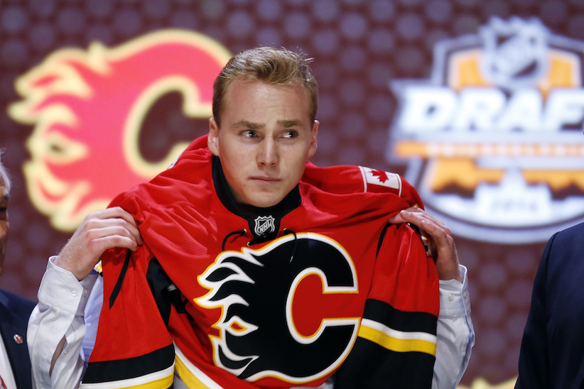 Samuel Bennett pulls on a Calgary Flames sweater after being chosen fourth overall during the first round of the NHL hockey draft, Friday, June 27, 2014, in Philadelphia. (AP Photo/Matt Slocum)